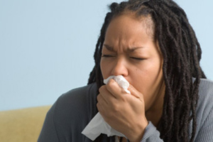 Woman coughing into handkerchief, indoors