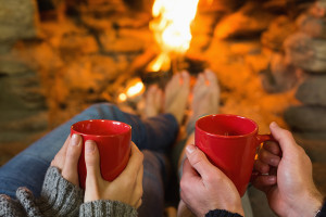 Close-up of hands holding red coffee cups in front of lit firepl