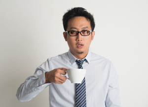 Tired Asian businessman with dark eyes circle holding coffee cup