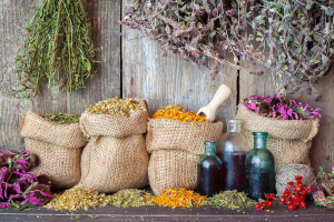 Healing Herbs In Hessian Bags And Bottles Of Essential Oil Near